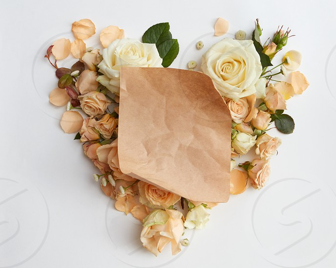 heart of roses flower and a piece of paper for your text on white background flat lay photo