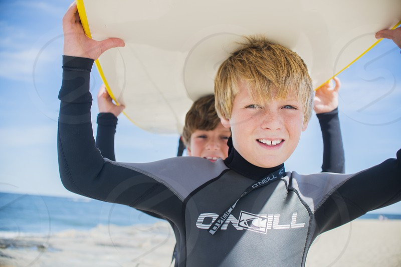2 boys in grey rash guards carrying white surfboard photo