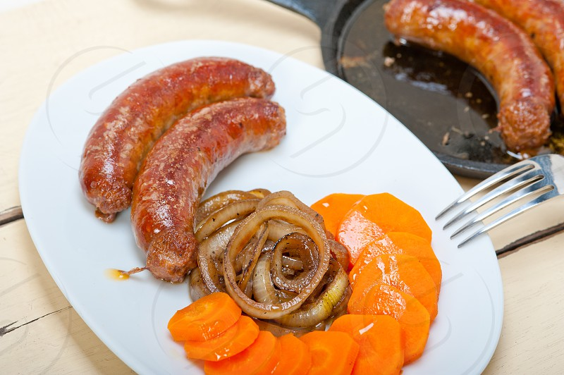 beef sausages cooked on iron skillet with carrot and onion photo