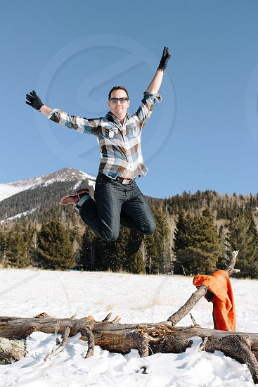 man jumping over the tree photo