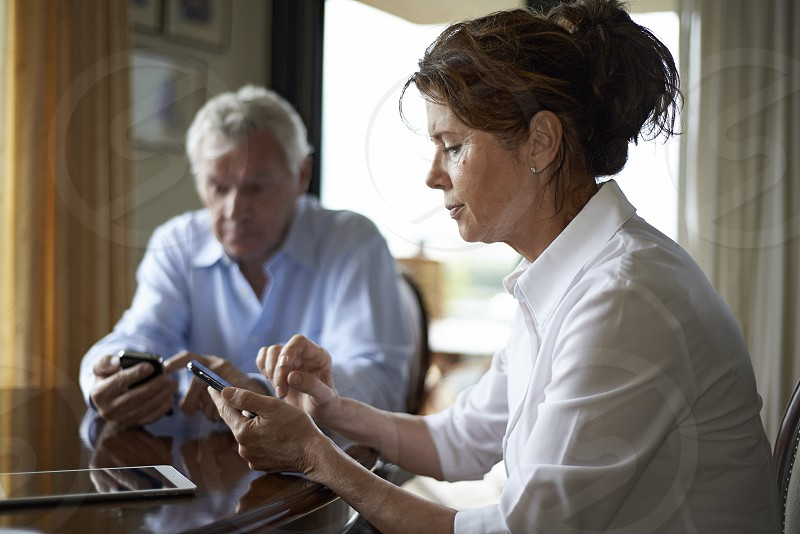Elderly couple sitting at the dinner table in their home each using their mobile phone to check messages and browse the internet photo