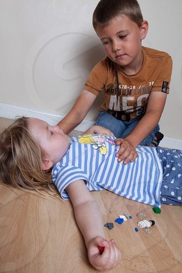 girl lying on the floor and boy assisting photo