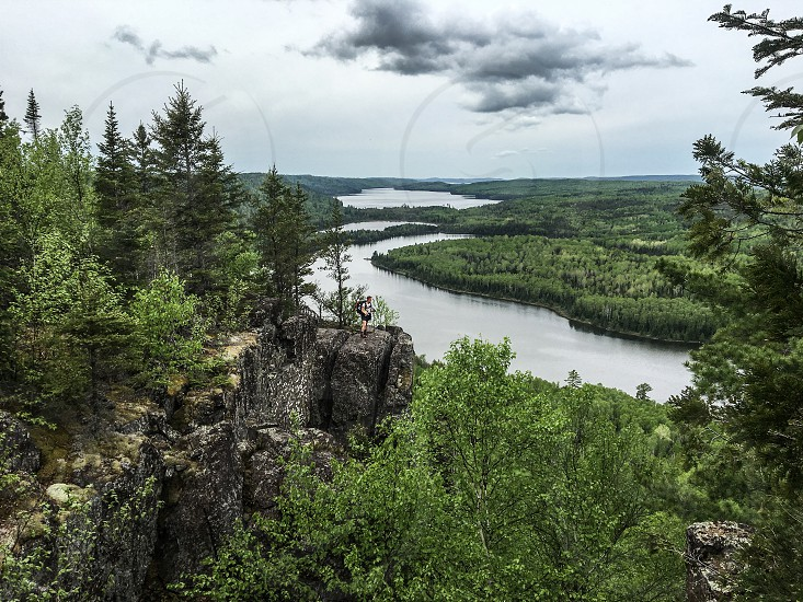 Northwoods looking over the wilderness with lakes and trees. Person standing on rocks looking out at landscape photo
