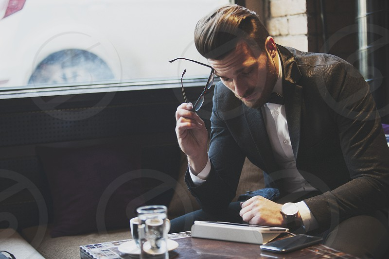 Man in fashion clothes with tablet mobile phone and coffee photo