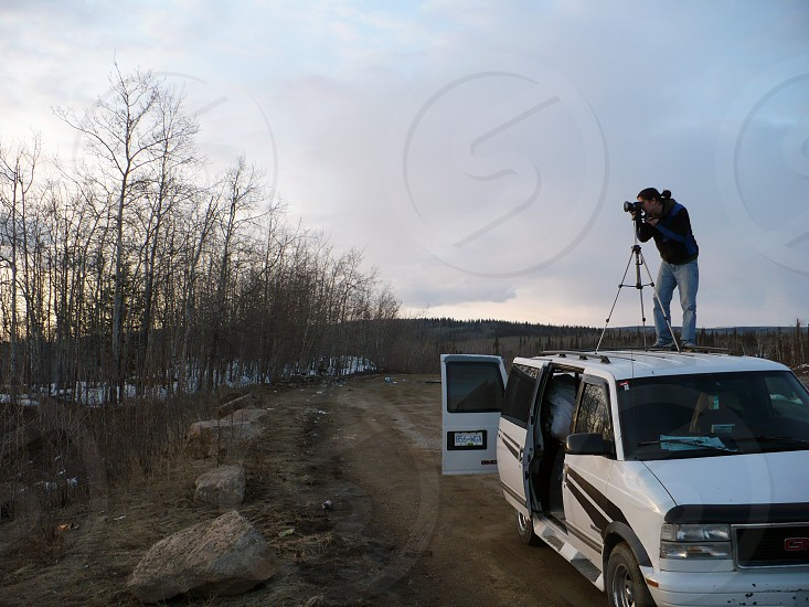 Taking photo on top of a car. Alaska USA. photo