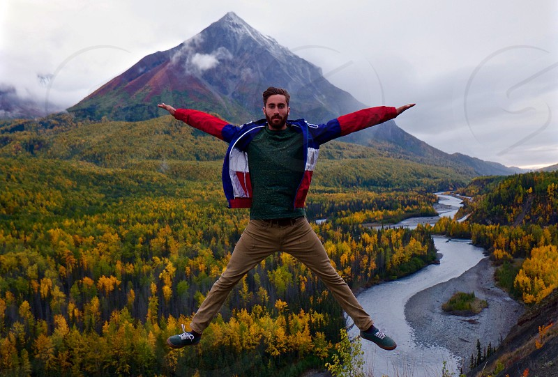 man in green shirt topped with blue white and red zip up jacket and brown pants jump shot on a green and yellow field with mountain behind photo