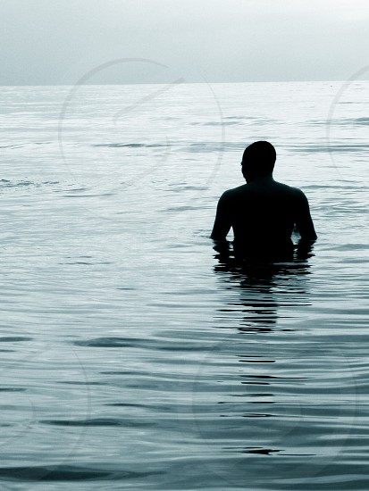 silhouette of man submerged up to waist in body of water at daytime photo
