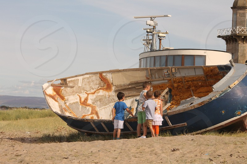 Children's fascination with old boat photo