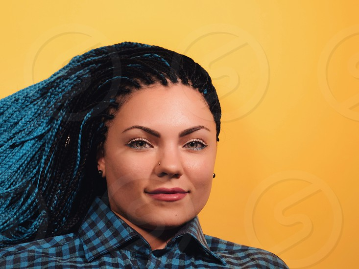 Beautiful young girl with african blue braids looks at the camera. Woman on bright yellow background. Dyed Hair moves. Hipster. photo