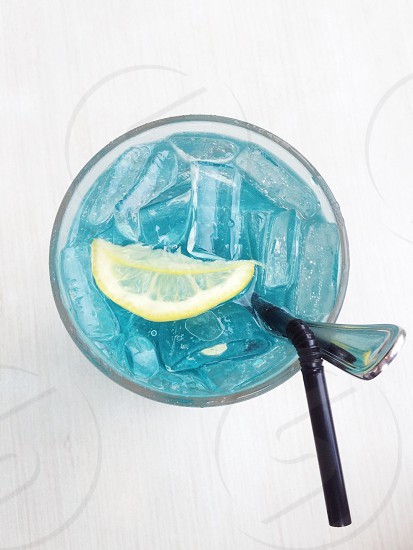 lemon wedge in a blue drink with a black straw and silver spoon photo