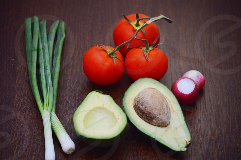 3 red tomatoes on brown wooden table above slice of avocado between green and white spring onions and red onions photo