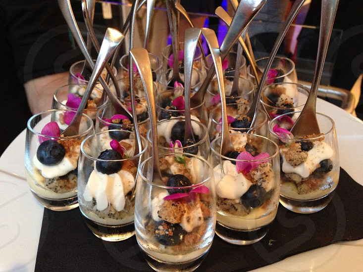 Blueberry crumble and whipped cream shotglass desserts with a silver spoon. photo