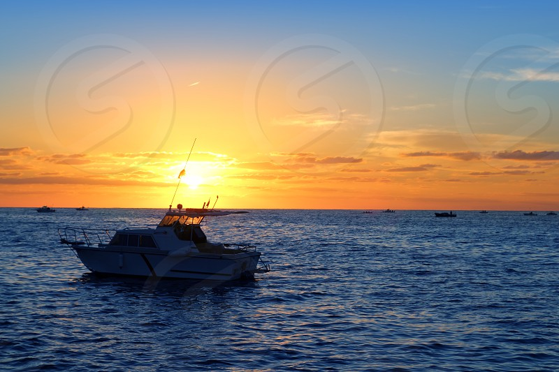 Sunrise fishing boat blue sea orange sky in Mediterranean photo