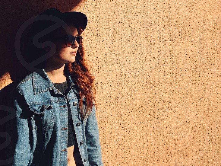 woman with brown long hair in blue denim jacket standing near brown wall during daytime photo