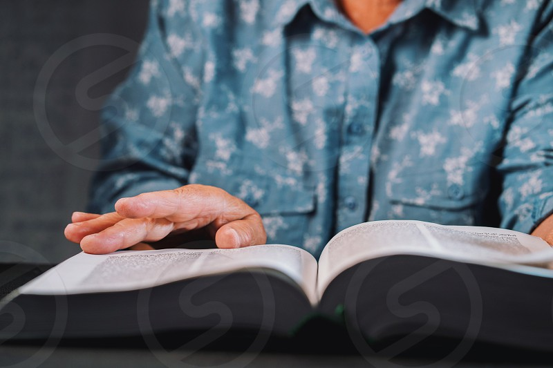 Old woman flipping through pages of book. Grandmother with Bible. Concentrated elderly pensioner with wrinkles on hands looking for information in the library. photo