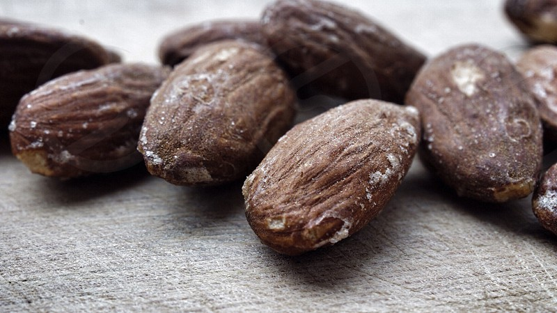 brown almond nuts on grey textile photo