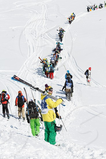 KAMCHATKA PENINSULA RUSSIA - MARCH 9 2014: Skiers and snowboarders climbing the mountain for freeride. Competition Kamchatka Freeride Open Cup. Eurasia Russian Far East Kamchatka Region. photo