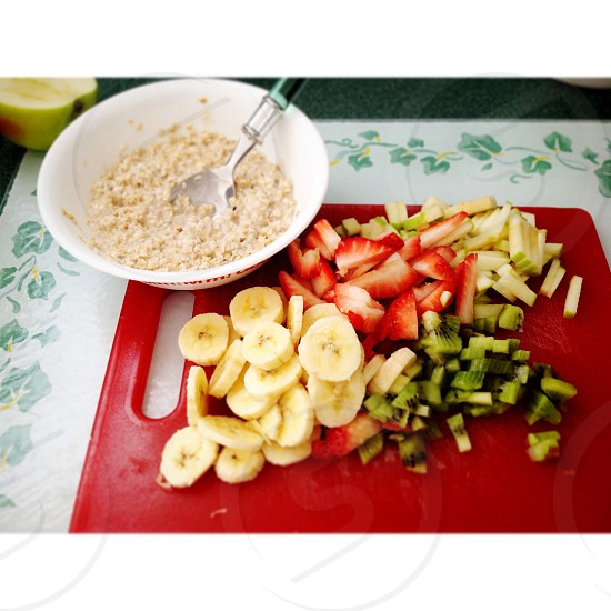 Oatmeal breakfast with strawberries kiwi green apple and bananas on cutting board. photo