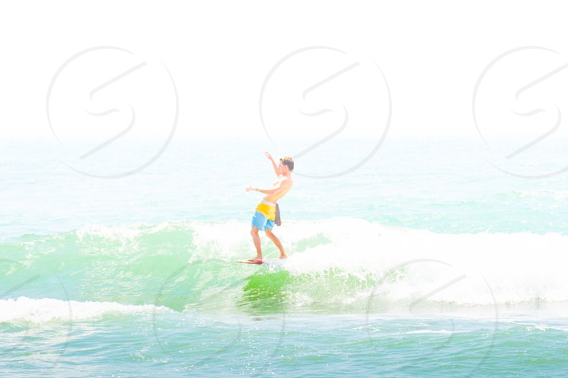 muted tones surfing surfer nose riding beach water sports photo