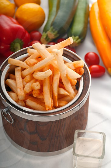 fresh french fries on a wood bucket with white dip sauce and fresh vegetables on background photo