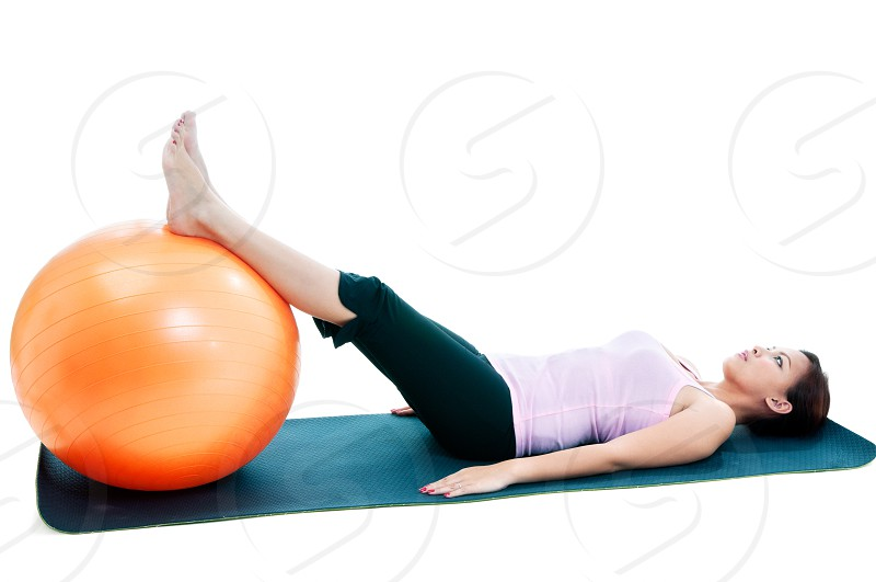 Fitness woman lying down with legs on balance ball. photo