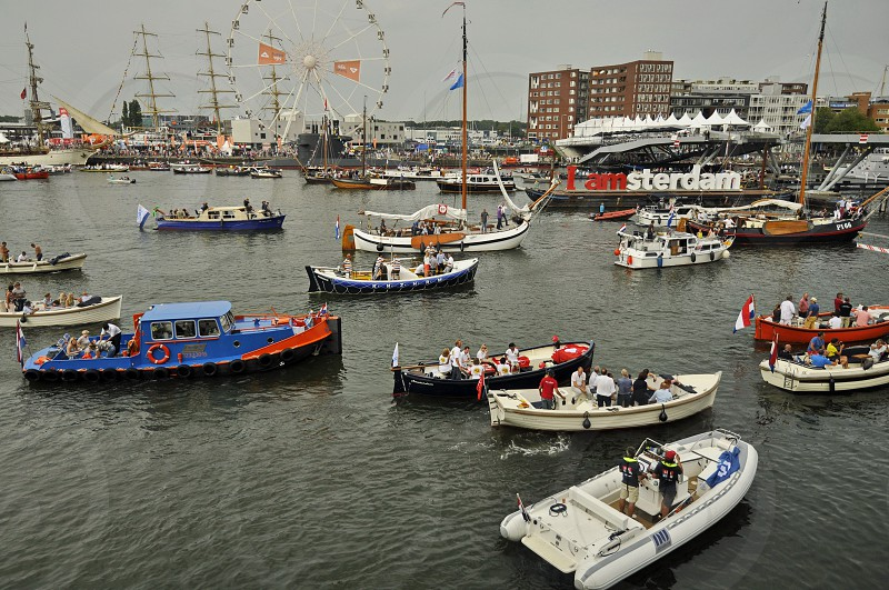 "Amsterdam the Netherlands - August 21 2015: Cruising passenger boats in the Ijhaven port and Amsterdam's official promotional sign the ""Iamsterdam"" display in the background at the time of the SAIL an international public nautical event held once in every 5 years since 1975. photo"