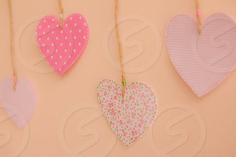 Heart-shaped cloth patches hanging on the wall. photo