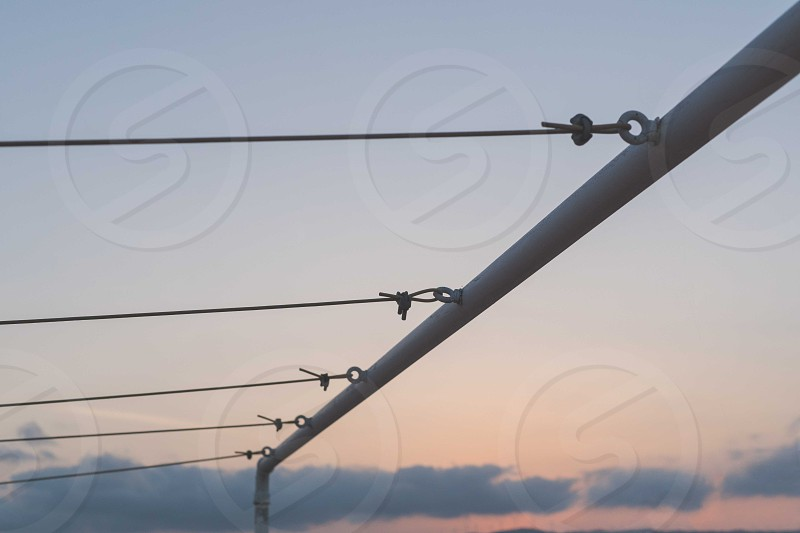 close up photography of gray steel with string under blue and gray cloudy sky during sunset photo