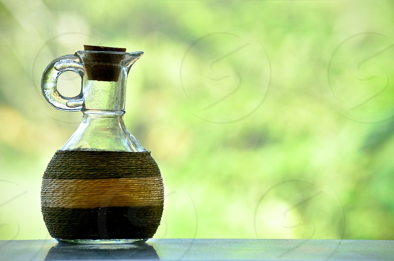 A Glass Jug in an off green blurred background. photo