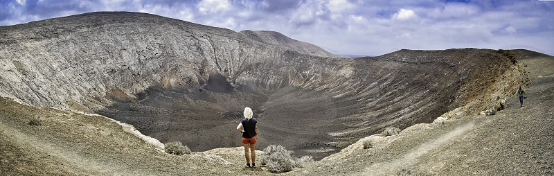 woman standing and watching crater photo