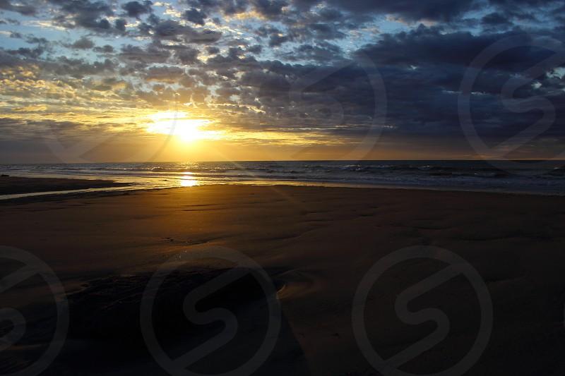 atlantic sunset sunrise beach sand reflection golden rock sand coast patagonia argentina south america sea ocean foam waves photo