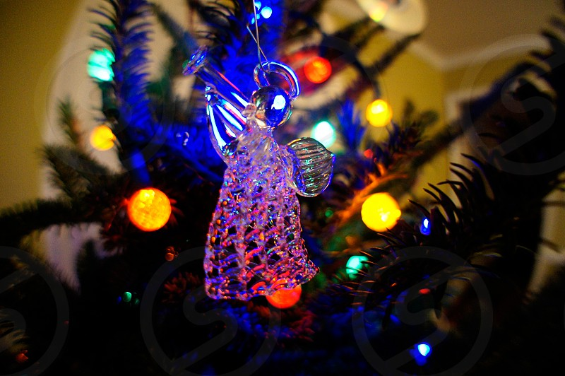 Glowing glass angel holiday ornament on a Christmas tree photo