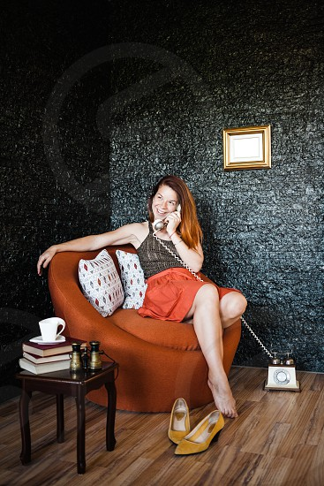 Young woman talking on the phone sitting in the armchair photo