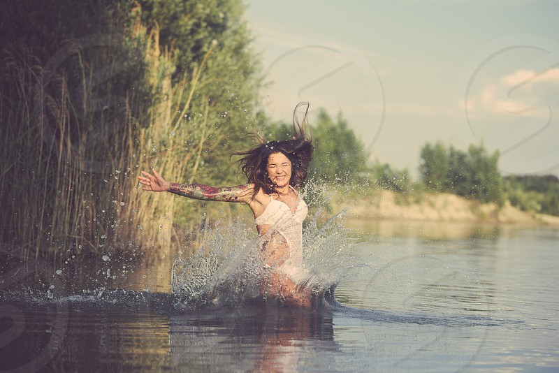 Young Tattooed Woman Jumping into Lake Water on a Summer Day photo