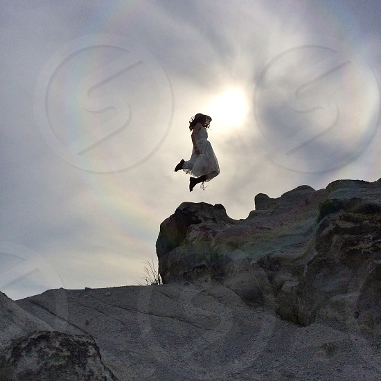 woman in white dress jumping above desert rocks photo