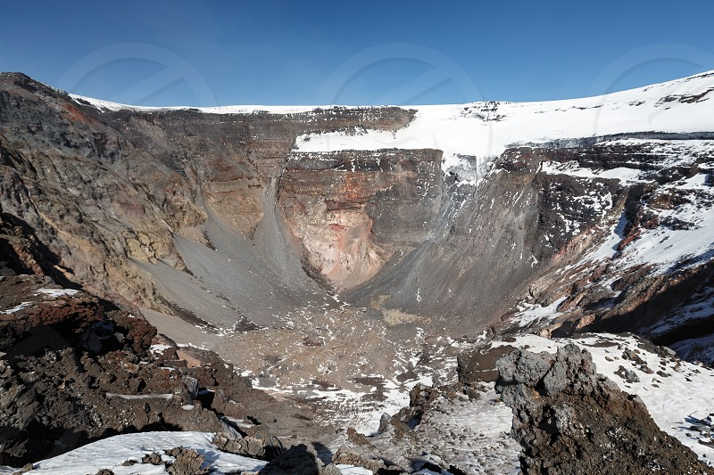 Volcanic landscape of Kamchatka Peninsula: view of large summit crater of active Tolbachik Volcano with steep sides and glaciers. Russian Far East Kamchatka Region Klyuchevskaya Group of Volcanoes. photo