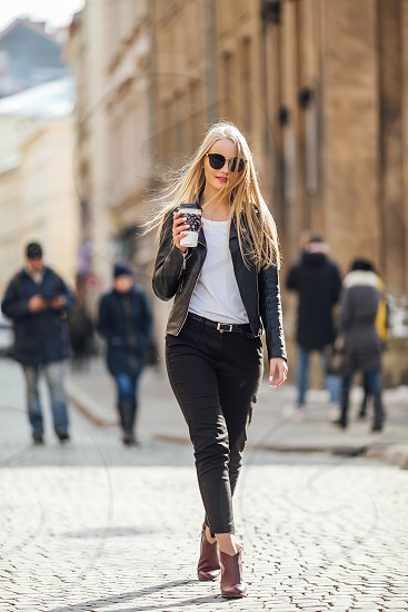 Young pretty girl walk on the street with cup of coffee on her hand and wear sunglasses sunny day weather photo