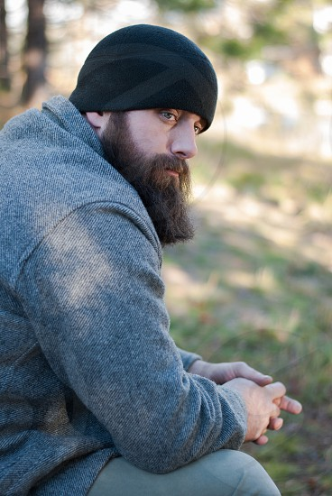 Bearded man sitting in outdoors with beanie on and looking contemplative photo