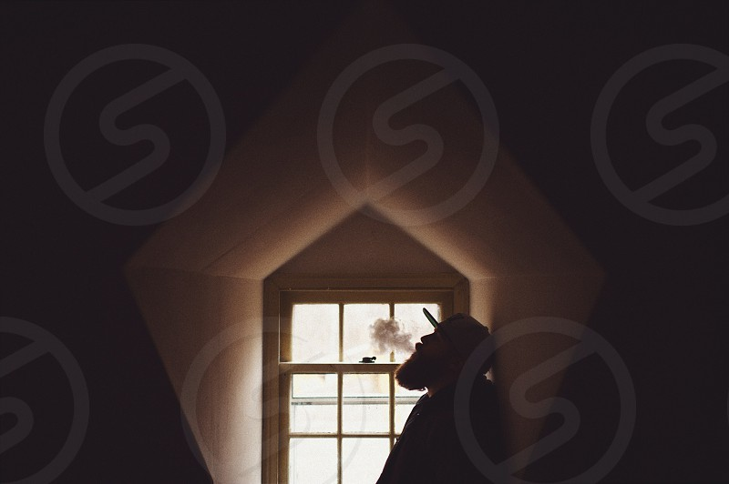 bearded man in baseball hat silhouetted against window photo