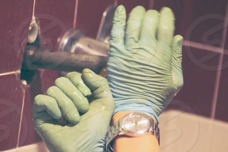 Gloved hands repairing a leaking shower fixture. photo
