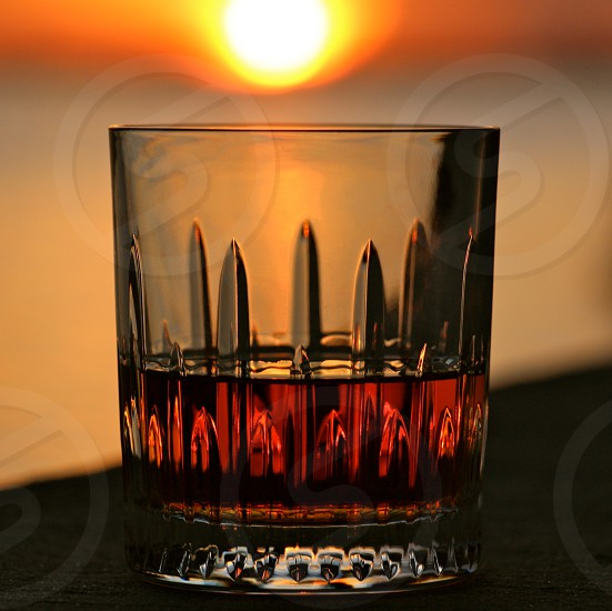 whiskey glass half full on a wall under a sunset sky photo