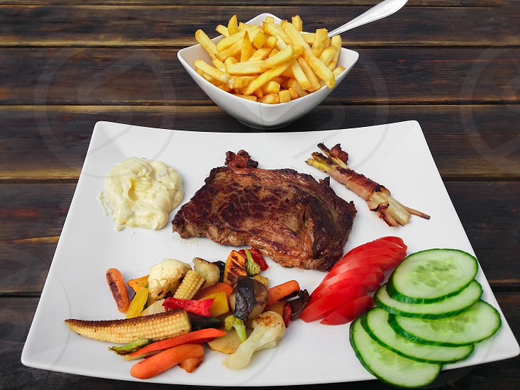 fried meat on plate with slices of tomato and cucumber wttih a side of fries photo