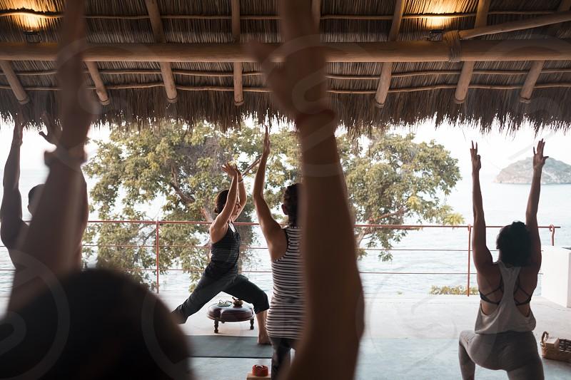 Group of multiple people practicing yoga on a palapa terrace. Yoga retreat Puerto Vallarta - Mismaloya Mexico photo