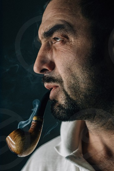 Portrait of a man smoking a pipe. photo