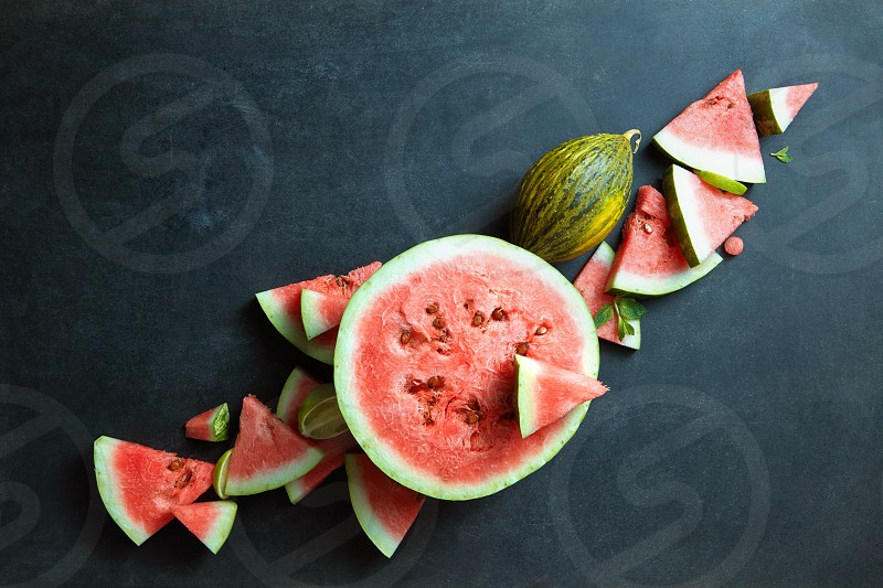 pieces watermelon and melon on a black background photo