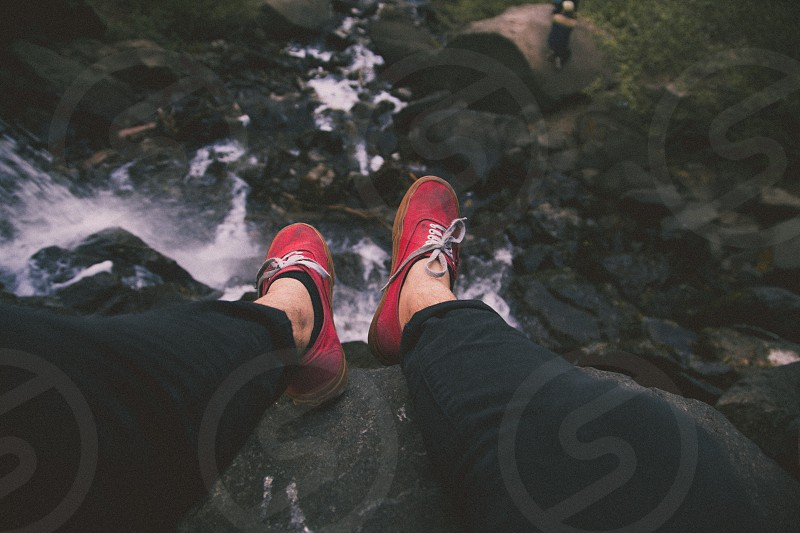 person in red and white lace up sneakers photo