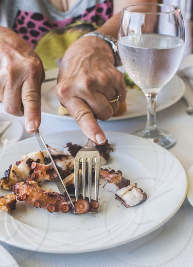 Octopus in a Greek restaurant. Hands are cutting octopus. Greece Athens Piraeus photo