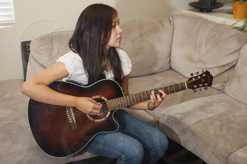 Teenage Navajo (Dineh) highschool girl plays six string acoustic guitar at home. Albuquerque NM photo