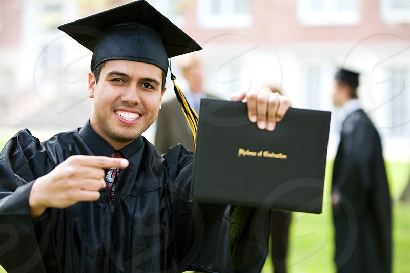 Hispanic male points to college diploma. photo