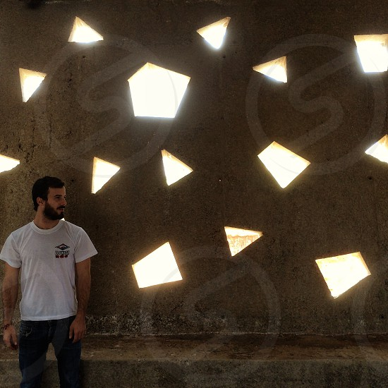person wearing white crewneck t-shirt standing near cement wall with light reflection photo